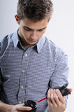 Young photographer cleaning lens. Young man, photographer cleaning lens Royalty Free Stock Images