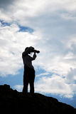 Young photographer girl silhouette. Silhouette of a young girl taking a photo with a DSLR Royalty Free Stock Images