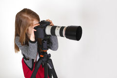Young photographer. Young girl taking photo using proffesjonal digital camera Stock Photo