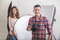 Young photographer with his beautiful assistant in studio. Portrait of young photographer with his beautiful assistant in studio ready for photo session Royalty Free Stock Photography