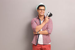 Young photographer holding a camera. Young cheerful photographer with a blue cap holding a camera and leaning against a gray wall Stock Photography