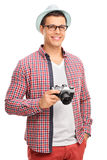 Young photographer holding a camera. Vertical shot of a young male photographer in artistic clothes holding a camera isolated on white background Stock Photos
