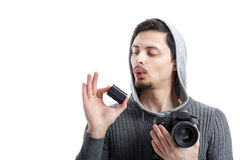 Young  photographer holds the battery for DSLR digital camera. Young  professional photographer in shirt  holds the battery for DSLR digital camera isolated on Stock Images