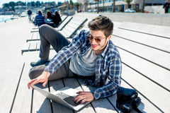 Young photographer with laptop and photo camera Royalty Free Stock Images