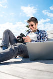 Young photographer with laptop and photo camera Royalty Free Stock Image