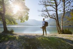 Young photographer looking at lake, on a beautiful sunny day stock images