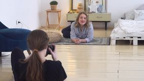 Young photographer in professional studio taking pictures of smiling model lying on the carpet. Professional photo. Young photographer in professional studio stock video footage