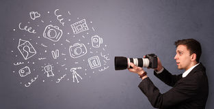 Young photographer shooting photography icons. Attractive young photographer shooting photography icons Royalty Free Stock Photo