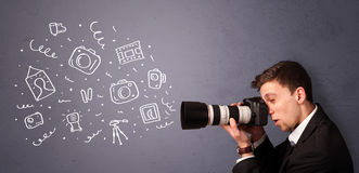 Young photographer shooting photography icons. Attractive young photographer shooting photography icons Stock Photo
