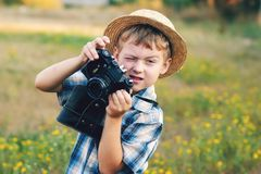 Young photographer in a straw hat with old camera. A little boy with an old camera .Young cheerful photographer royalty free stock image