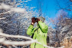 Young photographer takes pictures of winter forest using camera. Young man shooting photos outdoors. Young photographer takes pictures of winter forest using stock photo