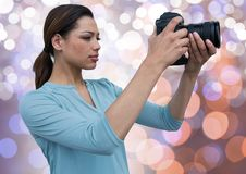 Young photographer taking a photo. Blue, orange and white bokeh background. Digital composite of young photographer taking a photo. Blue, orange and white bokeh Royalty Free Stock Images