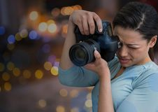 young photographer taking a photo. Blurred city lights at night behind Royalty Free Stock Photos