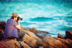 Young photographer taking photos at the beach Royalty Free Stock Image