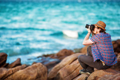 Young photographer taking photos at the beach Royalty Free Stock Images