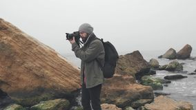 Young photographer taking photos of ocean cliff with DSLR camera stock video footage