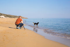 Young photographer and videographer making photos and videos of sea and his dog with the camera on a tripod. Mediterranean sea stock images