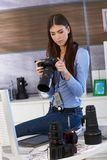 Young photographer at work. Checking camera, sitting on desk full of camera lens Royalty Free Stock Images
