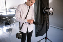 Young photographer work in studio. Man is setting photographing equipment in studio getting ready for a photo shoot stock photography