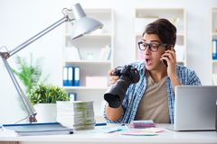 The young photographer working with his camera. Young photographer working with his camera Royalty Free Stock Photography