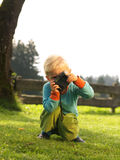 Young photographer. 3 years old child taking photo in the garden Stock Photo