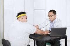 Young physician checks heartbeat of his fat patient stock photos