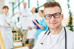 Young physician in medicine apprenticeship. With team of doctors royalty free stock photography