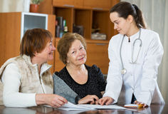 Young physician receiving mature patients in clinic Stock Photo