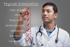 Young physician ticking physical examination checklist Royalty Free Stock Photos