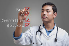 Young physician ticking the sports injury RICE checklist Royalty Free Stock Photography