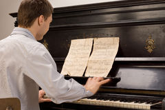 Young pianist sitting practicing at the piano Stock Images