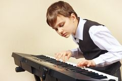 Young pianist in suit playing the electronic organ Stock Photos