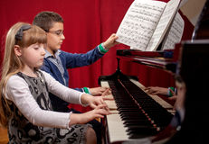 Young pianists,boy and girl playing a grand piano Royalty Free Stock Photos