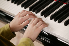 Young Piano Player. Young child playing the piano. Child's face is not shown; focus on child's hands on keys royalty free stock images