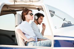 Young pilot and beautiful stewardess sitting inside airplane cabin Stock Images