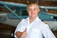 Young pilot with down syndrome showing thumbs up. Royalty Free Stock Image