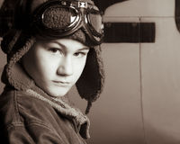Young Pilot with flight goggles. Young pilot with flight jacket / hat / goggles looking determined.  Standing in front of an airplane Royalty Free Stock Image