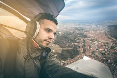 Young pilot flying an ultra light model above the city, Royalty Free Stock Images
