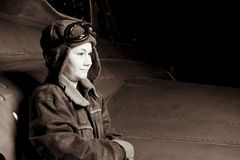 Young Pilot smiling off camera. A confident young pilot in flight jacket / hat / goggles is looking off to the side, room for copy space Royalty Free Stock Images