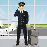 Young pilot talking on phone with luggage in front of an airport observation deck Stock Photos