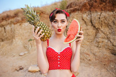 Young pin up girl posing with fruits in her hands Royalty Free Stock Photos