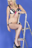 Young Pin Up Model Posing in Lingerie with Leg on Step Ladder Black Heels Looking Down Royalty Free Stock Photography