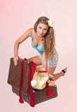 Young pin up woman tries to close a suitcase Royalty Free Stock Photos