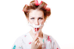 Young pinup housewife woman wearing curlers and shaving face Royalty Free Stock Images