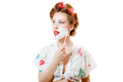Young pinup housewife woman wearing curlers and shaving face Royalty Free Stock Image