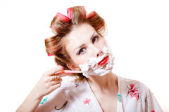 Young pinup housewife woman wearing curlers and shaving face stock images