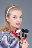 Young pinup woman with make up brushes Royalty Free Stock Photo