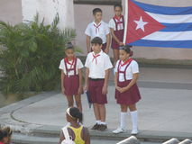 Young Pioneers with the Cuban Flag. Cuban school children (Young Pioneers) engage in the unfolding and raising of the Cuban flag Royalty Free Stock Images