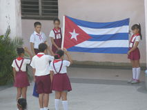 Young Pioneers with the Cuban Flag 2. Cuban School Children (Young Pioneers) salute the Cuban flag Royalty Free Stock Photos