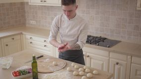 Young pizza maker in cook uniform pours olive oil on hand rolling dough balls for pizza in the kitchen. Food preparation. Young pizza maker in cook uniform pours stock video